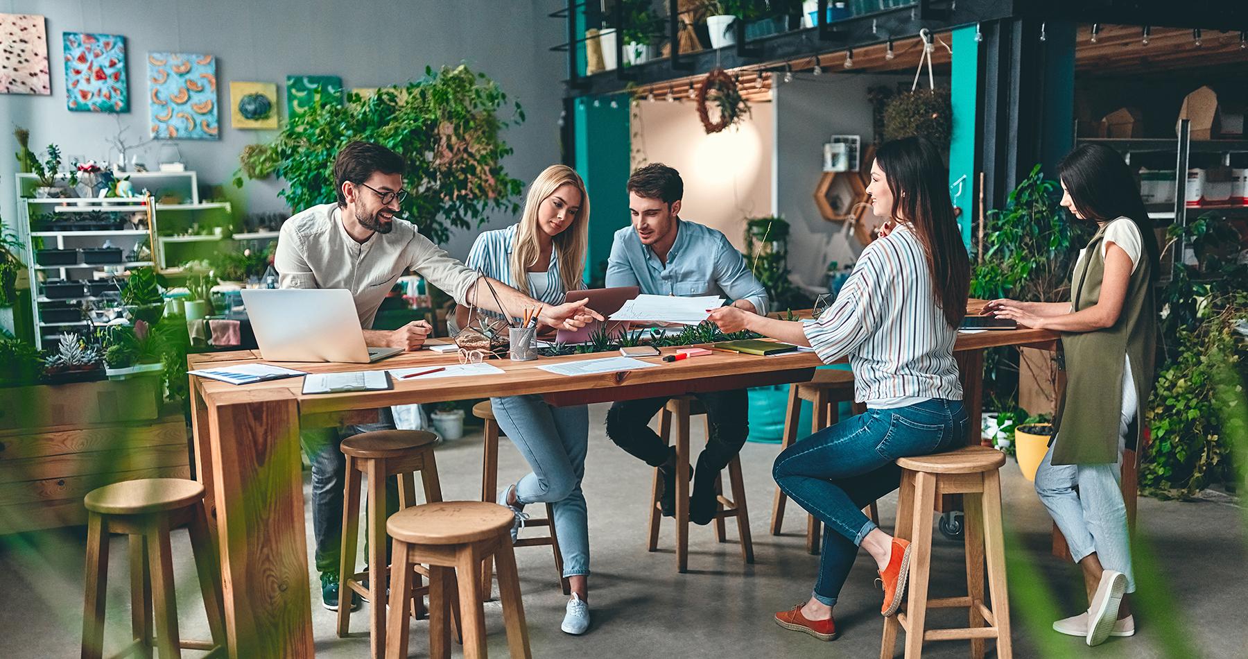 Groep jonge ondernemers die samenwerken in een modern, groen en duurzaam kantoor. Creatieve personen met laptop, tablet, smart phones