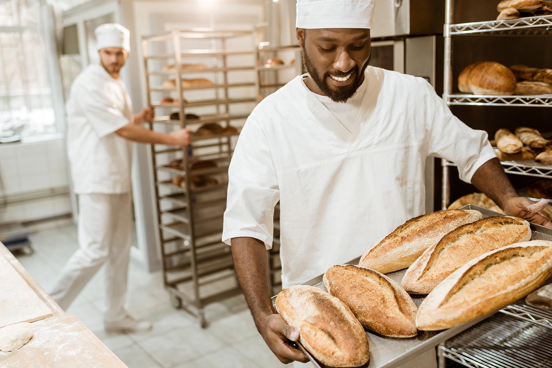 Een bakker die diverse broden uit de oven haalt in een bakkerij
