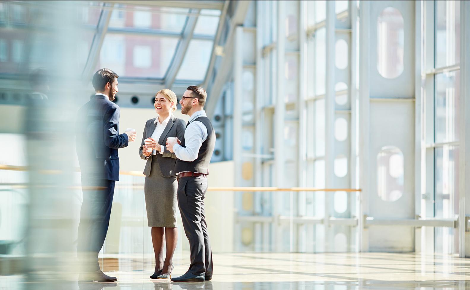 Groep moderne zakelijk geklede mensen in gesprek met een kop koffie in een door de zon verlichte hal of bedrijfspand.